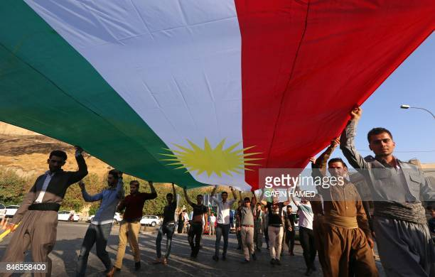 Iraqi Kurds holds a large Kurdish flag as they walk near the citadel towards a gathering urging people to vote in the upcoming independence...