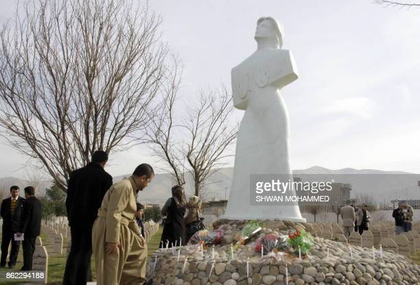 Iraqi Kurds light candles and lay flowers at a monument in the cemetery for the victims of a gas attack in the northern Iraqi town of Halabja on...