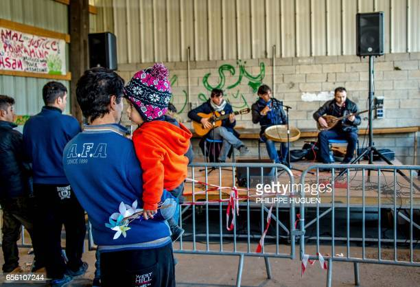 Iraqi Kurds listen at musicians in La Liniere camp in GrandeSynthe northern France on March 21 during the celebrations of Newroz 'New day' the first...