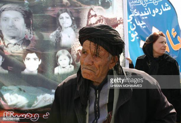 Iraqi Kurds look at posters as they attend a ceremony in the Kurdish town of Halabja in nothern Iraq in remembrance of the town's victims on March 16...
