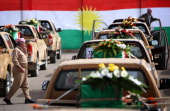 Iraqi Kurds stand near vehicles carrying some of the 93 coffins draped with the Kurdish flag and containing the recently exhumed remains of victims...