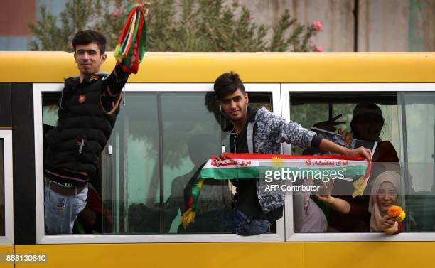 Iraqi Kurds wave fabrics with the colour of the Kurdish flag during a protest in support of the Iraqi Kurdish leader in Arbil the capital of...