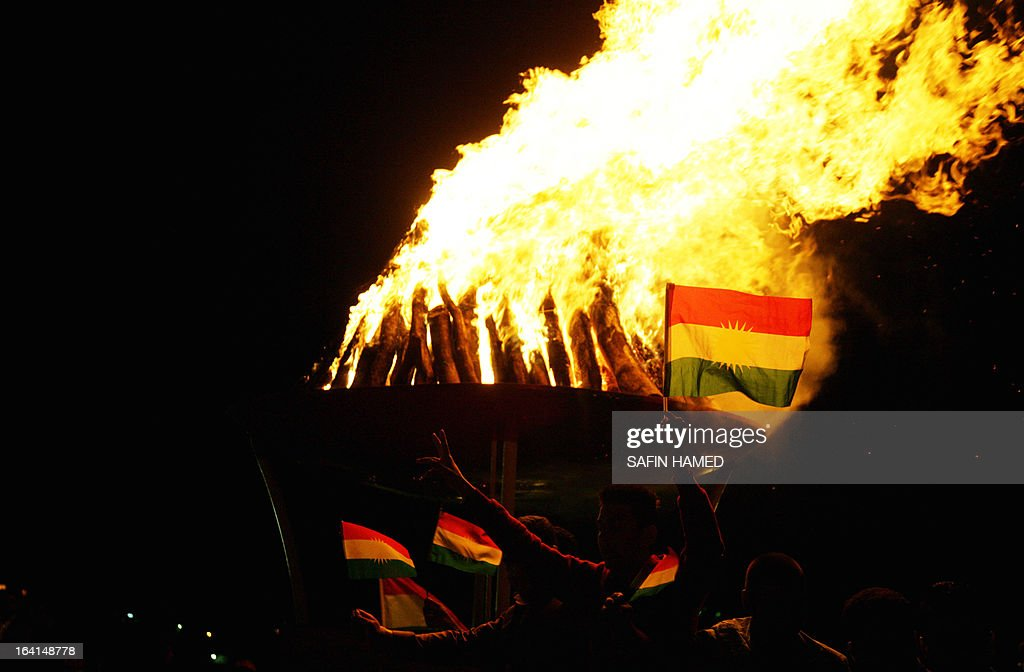 Iraqi Kurds wave the Kurdish flags next to a bonfire to celebrate new year which marks the beginning of the Noruz spring festival in the northern city of Arbil, the capital of the autonomous Kurdistan region, on March 20, 2013. The Persian New Year is an ancient Zoroastrian tradition celebrated by Iranians and Kurds which coincides with the vernal (spring) equinox and is calculated by the solar calender.