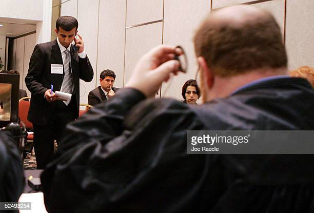 Iraqi law student Rebaz Khurshed Mohammed and President of the court Judge Laurence Jortner adjust their headsets to hear the interpreter during the...