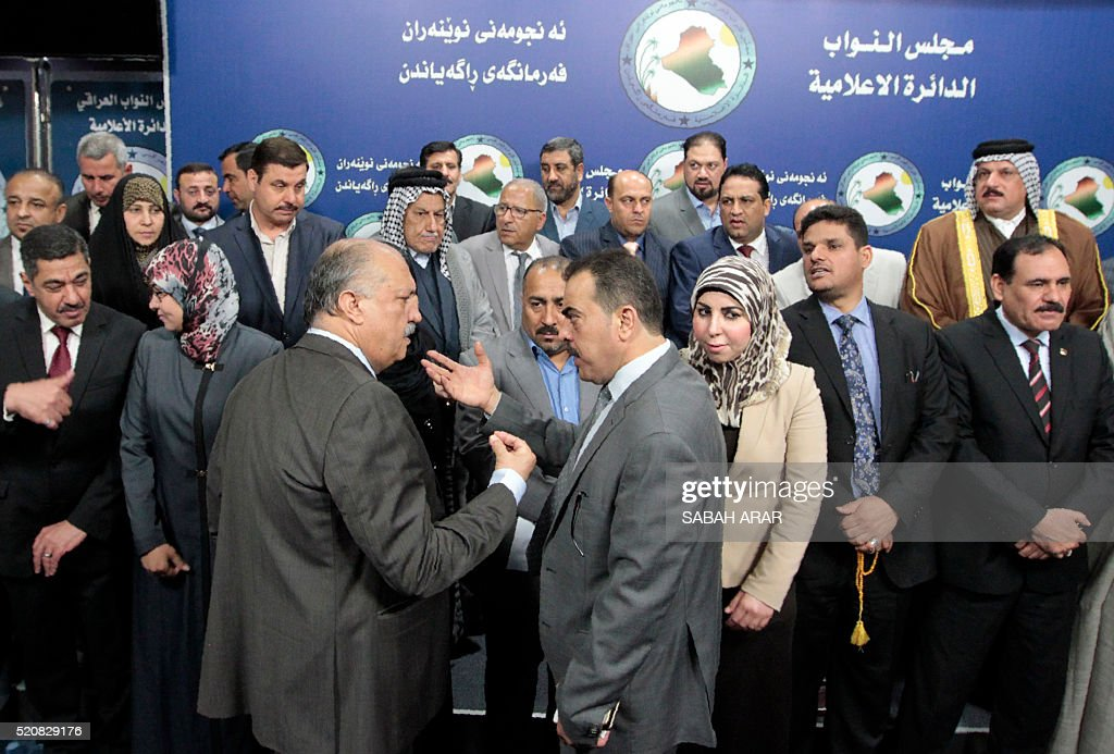 Iraqi lawmakers prepare to pose for a picture during a sitin inside the parliament in Baghdad on April 13 to protest against the system of ministries...