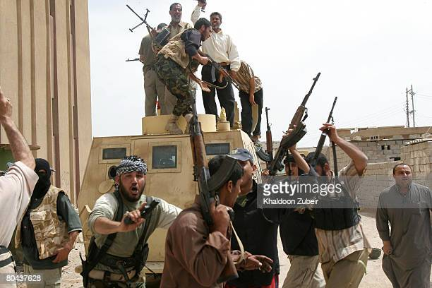Iraqi Madhi army militiamen dance as they stand near a burning Iraqi army vehicle after attacking it on March 30 2008 in the city of Basra 370 miles...