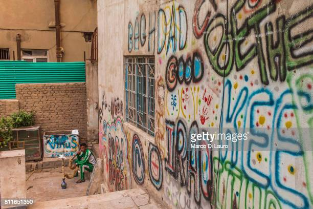 A iraqi man smokes shisha from a narghile next to some graffiti on the wall of the Burj Babel Art Gallery on April 18 2015 in Baghdad Iraq
