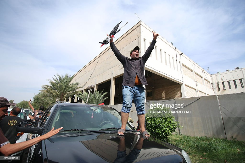 A Iraqi man stands on a vehicle as protesters gather outside the parliament after braking into Baghdad's heavily fortified 'Green Zone' on April 30, 2016. A protest held outside the Green Zone escalated after parliament again failed to reach a quorum and approve new ministers to replace the current government of party-affiliated ministers. / AFP / HAIDAR