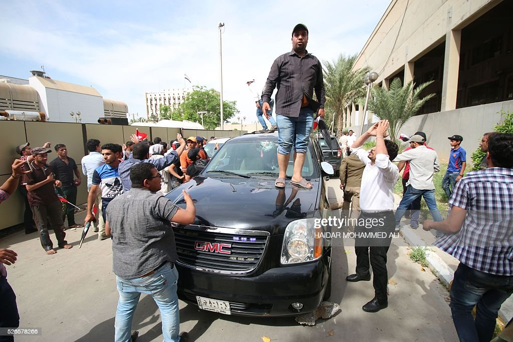 A Iraqi man stands on a vehicle as protesters gather outside the parliament after breaking into Baghdad's heavily fortified 'Green Zone' on April 30, 2016. Thousands of angry protesters broke into Baghdad's Green Zone and stormed the parliament building after lawmakers again failed to approve new ministers. Jubilant supporters of cleric Moqtada al-Sadr invaded the main session hall, shouting slogans glorifying their leader and claiming that they had rooted out corruption. / AFP / HAIDAR