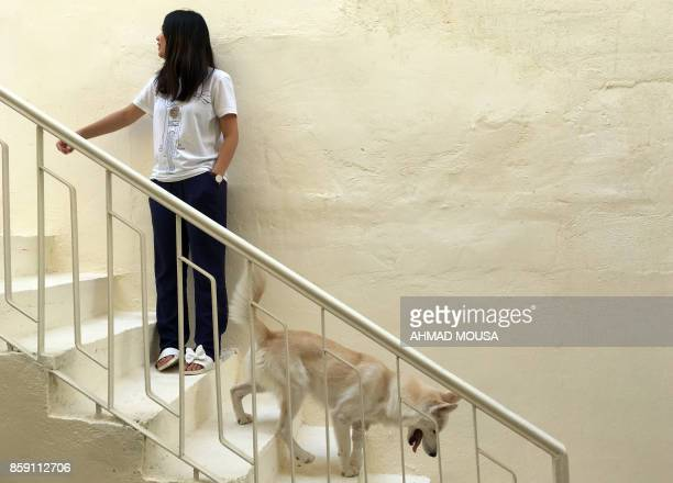 Iraqi Marina Jaber is seen with her dog Majnoona which means crazy in Arabic at her home in Baghdad on September 22 2017 Majnoona was adopted by...
