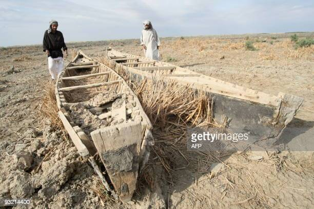 Iraqi marsh Arabs look at their dilapidated wooden dug out canoes lying in the dried out Hor or marshes some 130 km southwest of the southern city of...
