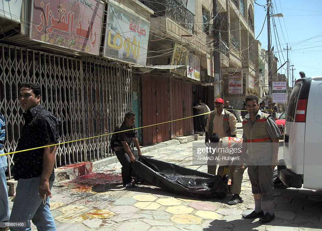 Iraqi medical workers remove the body of a jewellers following a robbery shootout in Baghdad on May 25, 2010. Gunmen swooped on Baghdad jewellers in a morning rampage, killing 14 people and bombing almost a dozen stores after robbing them, an interior ministry official said.