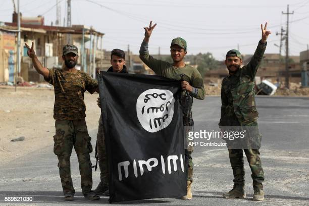 Iraqi members of the Hashed alShaabi carry an upsidedown Islamic State group flag in the city of alQaim in Iraq's western Anbar province near the...
