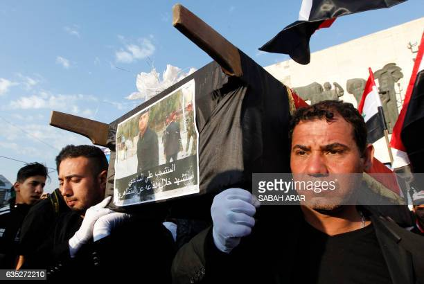 Iraqi men carry a mock coffin during a rally mostly attended by supporters of prominent cleric Moqtada Sadr in Baghdad on February 14 to pay their...