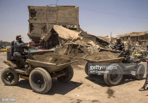 Iraqi men clear the rubble in west Mosul on July 12 2017 after the government declared it had driven the Islamic State group jihadists from their...