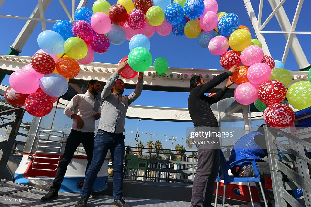 Iraqi men decorate a stage ahead of Valentine's day celebrations at Baghdad's Al-Zawraa Park, on February 14, 2016. / AFP / Sabah ARAR