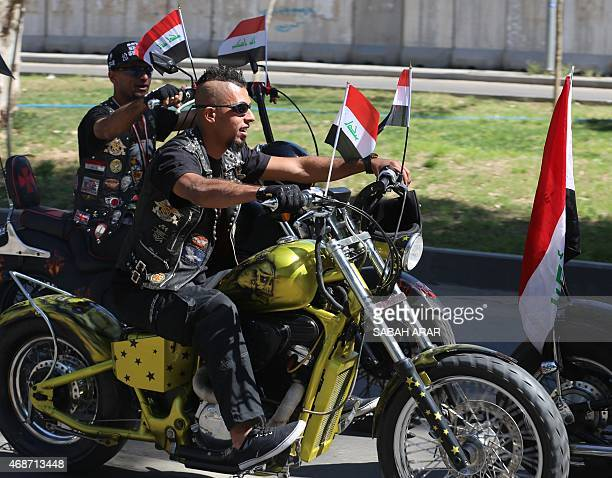 Iraqi men drive their motorbikes flying their national flag during Baghdad's Abu Nawas street marathon in support of security forces and the popular...