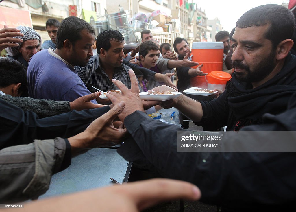 Iraqi men hand out plates of food to Muslim Shiite pilgrims as believers begin to gather for the upcoming Ashura rituals in Baghdad, on November 20, 2012. Ashura mourns the death of Imam Hussein, a grandson of the Prophet Mohammed, who was killed by armies of the caliph Yazid near Karbala in 680 AD.