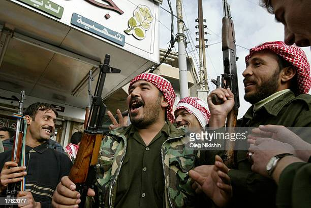Iraqi men hold an AK47 rifle before a parade in Mosul north of Baghdad February 4 2003 Thousands of armed volunteers paraded in northern Iraq in...