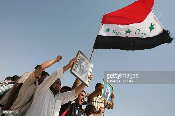 Iraqi men hold up a portrait of Shiite Sheikh Adel Harrat alTimini a member of the alTimini tribe whom they say was arrested by the US military 02...