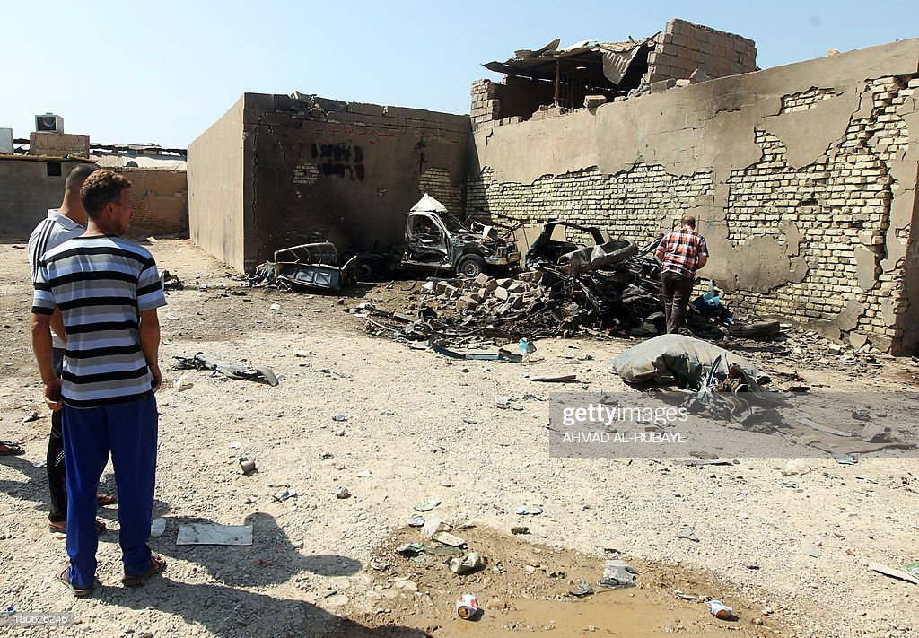Iraqi men inspect the site of a car bomb explosion in the city of Suweirah, south of Baghdad, on September 15, 2013. A wave of attacks across Iraq, including more than a dozen car bombs, killed at least 30 people while the head of Baghdad's provincial council escaped assassination.