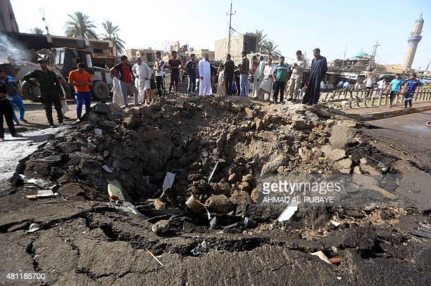 Iraqi men look at a crater left by a massive suicide car bomb attack carried out the previous day by the Islamic State group in the predominantly...