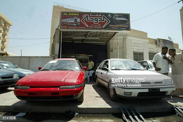 Iraqi men look at cars parked on the sidewalk that are for sale outside a car dealership in Baghdad 21 June 2003 The USled administration in Iraq has...