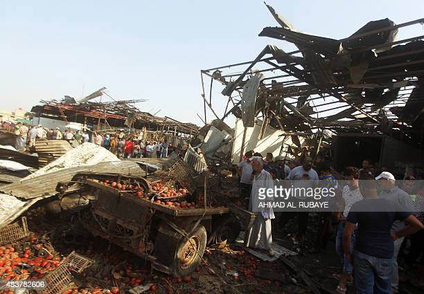 Iraqi men look at the damage following a bomb explosion that targeted a vegetable market in Baghdad's northern Shiite district of Sadr City on August...