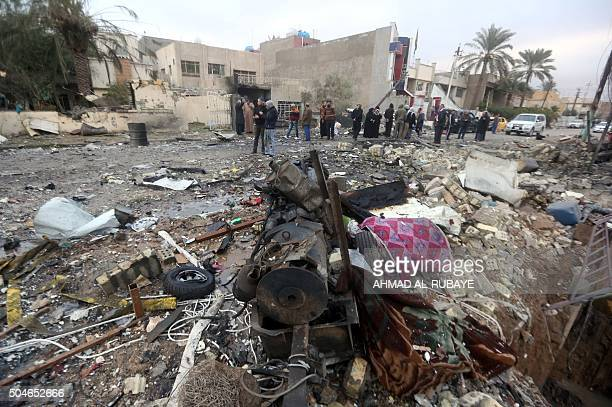Iraqi men look at the damage near the alJawaher mall in eastern Baghdad the day after a bomb attack on January 12 2016 Jihadist gunmen and bombers...