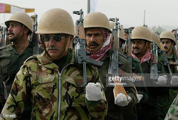 Iraqi men march during a parade in Mosul north of Baghdad February 4 2003 Thousands of armed volunteers paraded in northern Iraq in defiance of US...