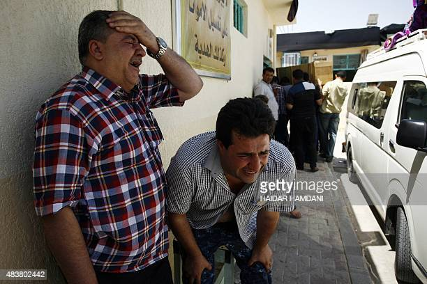 Iraqi men mourn outside a mosque in the holy city of Najaf on August 13 2015 during the funeral of Shiite victims of this morning's truck bombing in...