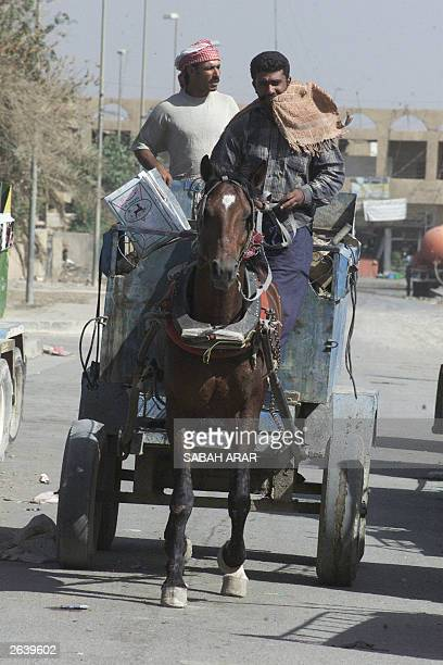 Iraqi men on a horsedrawn cart wait for the truck that is due to deliver propane gas from a refinery in Baghdad 23 October 2003 Jobs already were...