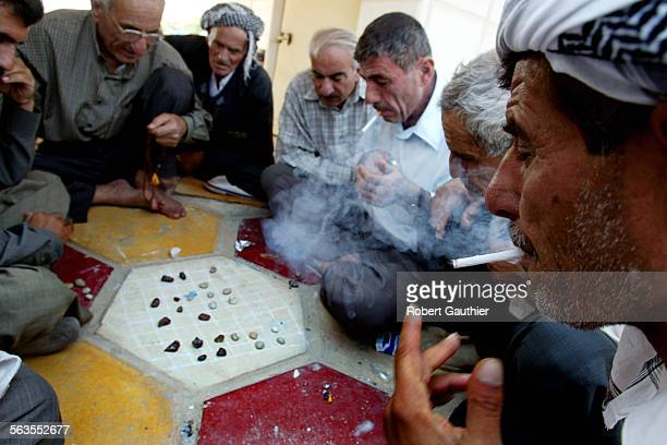 Iraqi men play a strategy game called 'Dama' in a public plaza in Kirkuk Iraq Tuesday October 15 2002 Photo/Art ^^^/Los Angeles Times