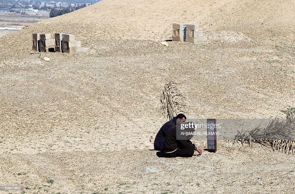 Iraqi men sitting at the grave of their brother, a former policeman who was killed by al-Qaeda sympathizers in 2008 in the Anbar province, at a cemetery in western town of Fallujah, 50 kilometers from Baghdad, on January 16, 2013.