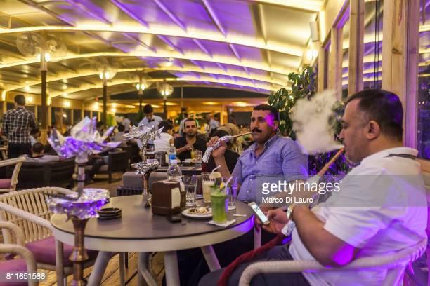 Iraqi men smoke shisha from a narghile at the Jadriya Floating Restaurant on April 23 2015 in Baghdad Iraq'n