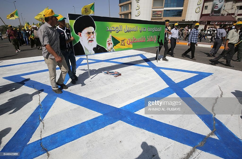 Iraqi men stand on an Israeli national flag and hold a banner depicting a portrait of Iran's supreme leader Ayatollah Ali Khamenei as they take part in a parade marking al-Quds (Jerusalem) Day in the capital Baghdad, on July 1, 2016. RUBAYE