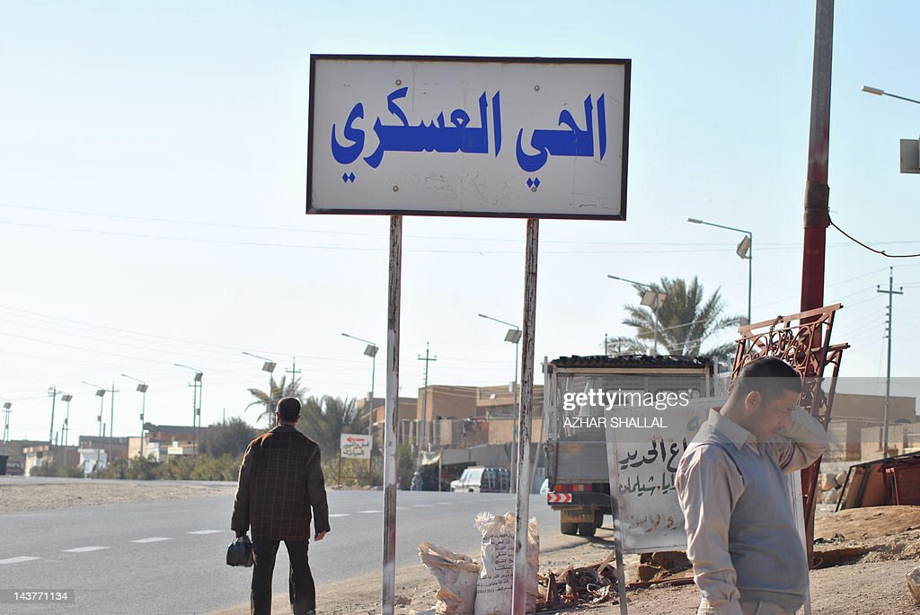 Iraqi men stand under a sign which reads in Arabic 'The Military District' on January 24, 2012 in Haditha, a town of around 80,000 people in the western Iraq Anbar province, where 24 Iraqis were killed by US troops in 2005. Haditha residents and relatives of those killed by US troops in 2005 have voiced shock and disgust over the light sentence meted out to a US soldier involved in the massacre.