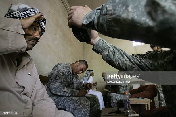 Iraqi men stretch their eyes as US soldiers scan their irises using a biometrics digital system camera during an enlistment program session to join...