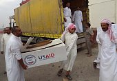 Iraqi men unload humanitarian aid supplies provided by the US development agency USAID to displaced Iraqis who have fled clashes between Islamic...