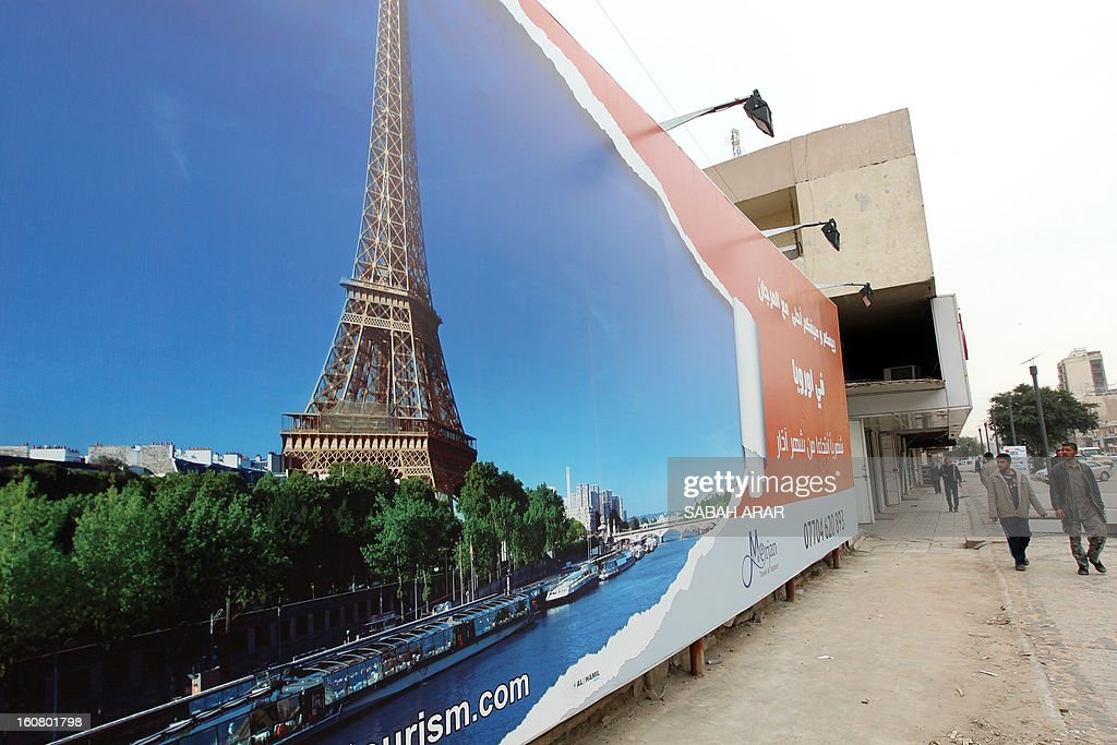 Iraqi men walk past a giant advert making the promotion of a travel agency organizing trips to Paris, a new destination for the country, on February 6, 2013 in the Iraqi capital, Baghdad. Iraqis are now allowed to ask for European visas. AFP PHOTO SABAH ARAR