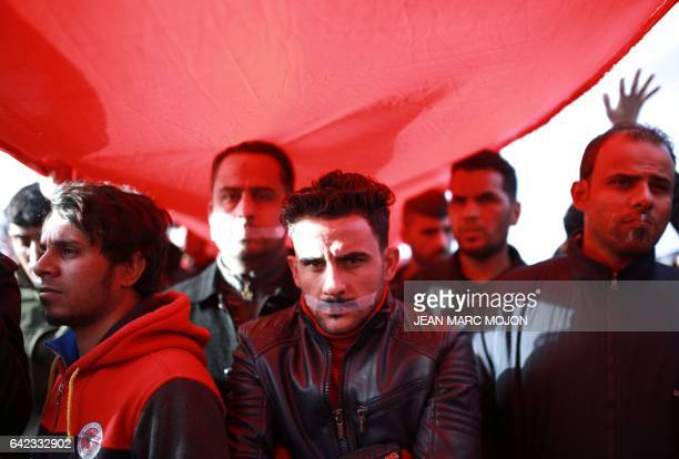 TOPSHOT Iraqi men with duct tape across their mouthes take part in a silent protest of mostly supporters of prominent cleric Moqtada Sadr on February...