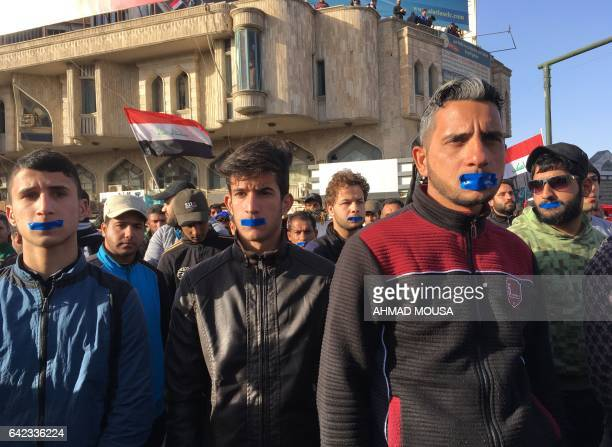 Iraqi men with duct tape across their mouths take part in a silent protest of mostly supporters of prominent cleric Moqtada Sadr on February 17 2017...