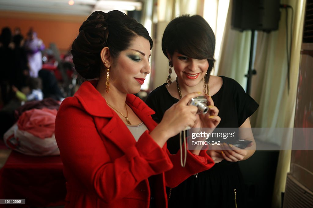 Iraqi models share their pictures backstage during a hairdressers and make up artists festival on February 9, 2013 in Baghdad. It is the first time that this kind of festival takes place in the Iraqi capital since 1999.