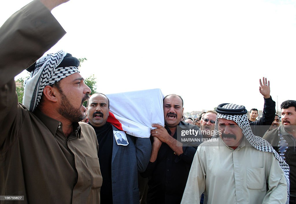 Iraqi mourners carry the body of Shiite police inspector Qassem Abdellatif during his funeral in the northern Iraqi city of Kirkuk on November 20, 2012. The inspector was killed along with one of his brothers by a car bomb explosion in the multi-ethnic city the night before. S