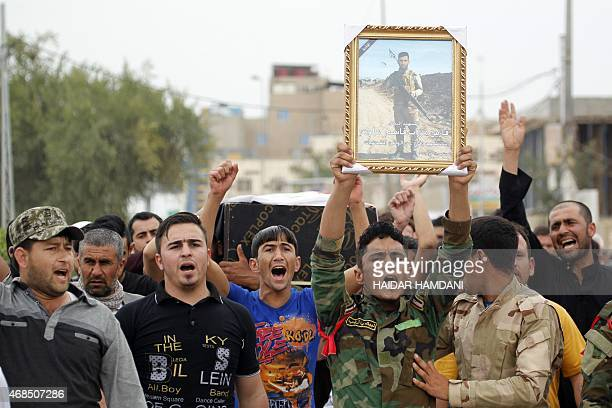 Iraqi mourners carry the coffin and portrait of a member of the Popular Mobilisation units who died in combat against Islamic State group fighters in...