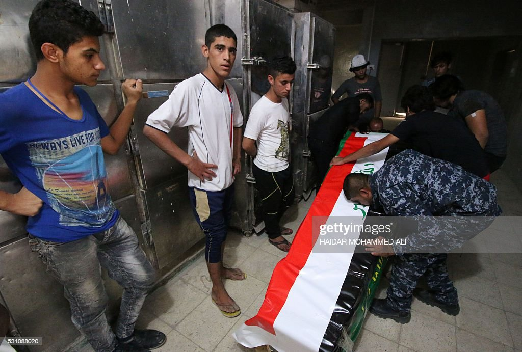 Iraqi mourners prepare the coffin of a man who was killed fighting alongside Iraq government forces to retake to city of Fallujah from jihadists of the Islamic State group, on May 25, 2016 before his funeral in the southern city of Basra. Iraqi forces battled the Islamic State group in the opening stages of an operation to retake Fallujah, one of the toughest targets yet in Baghdad's war against the jihadists. ALI