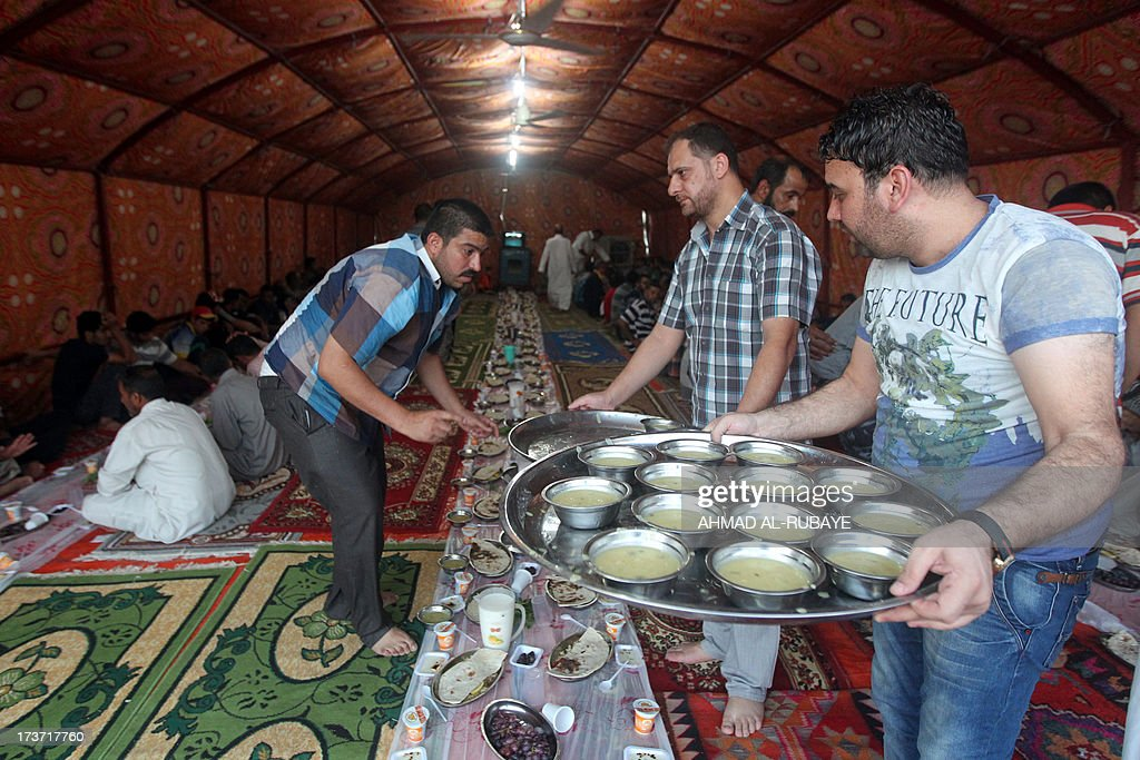 Iraqi Muslim men distribute food before breaking their fast in a meal known as Iftar inside a tent dedicated to cooking and eating during Ramadan, which is the first of its kind in the capital Baghdad. A group of Iraqi businessmen are providing free Iftar meals for poor people during Islam's holy fasting month of Ramadan where observers must abstain from food, drink and sex from dawn to dusk.