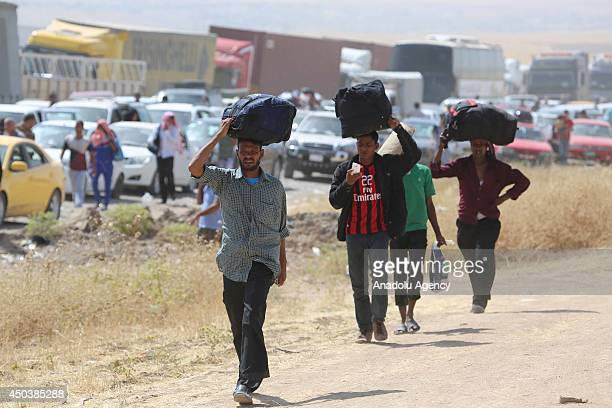 Iraqi people carry their properties while fleeing from Mosul to Arbil and Duhok due to the clashes between security forces and militants of Islamic...