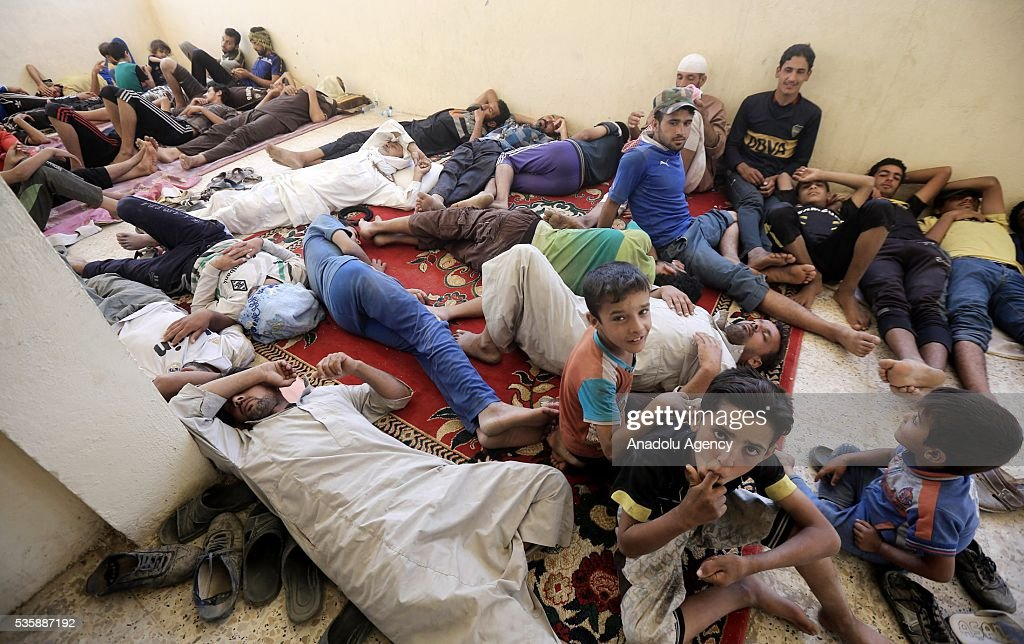 Iraqi people sleep on a carpet as they leave their home in Fallujah town due to conflicts between Daesh and security forces in Anbar, Iraq on May 30, 2016. Some of the families who left their home are placed in a school in Karma Town, west of Anbar city.