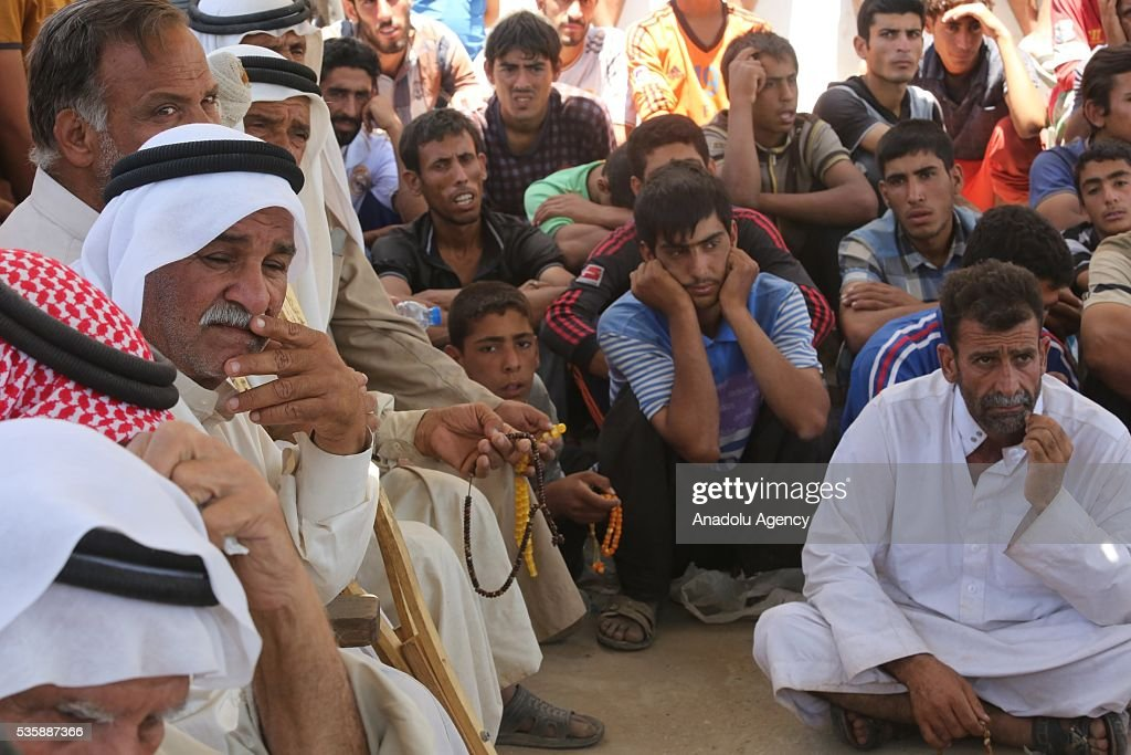 Iraqi people stand as they leave their home in Fallujah town due to conflicts between Daesh and security forces in Anbar, Iraq on May 30, 2016. Some of the families who left their home are placed in a school in Karma Town, west of Anbar city.